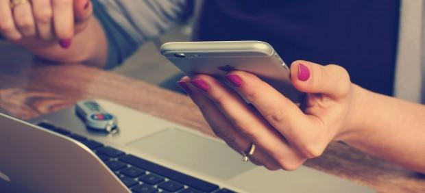 Imagen de archivo de una mujer usando el móvil y el ordenador